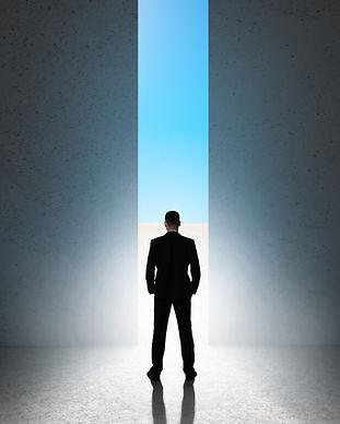 Silhouette of man against giant doorway.