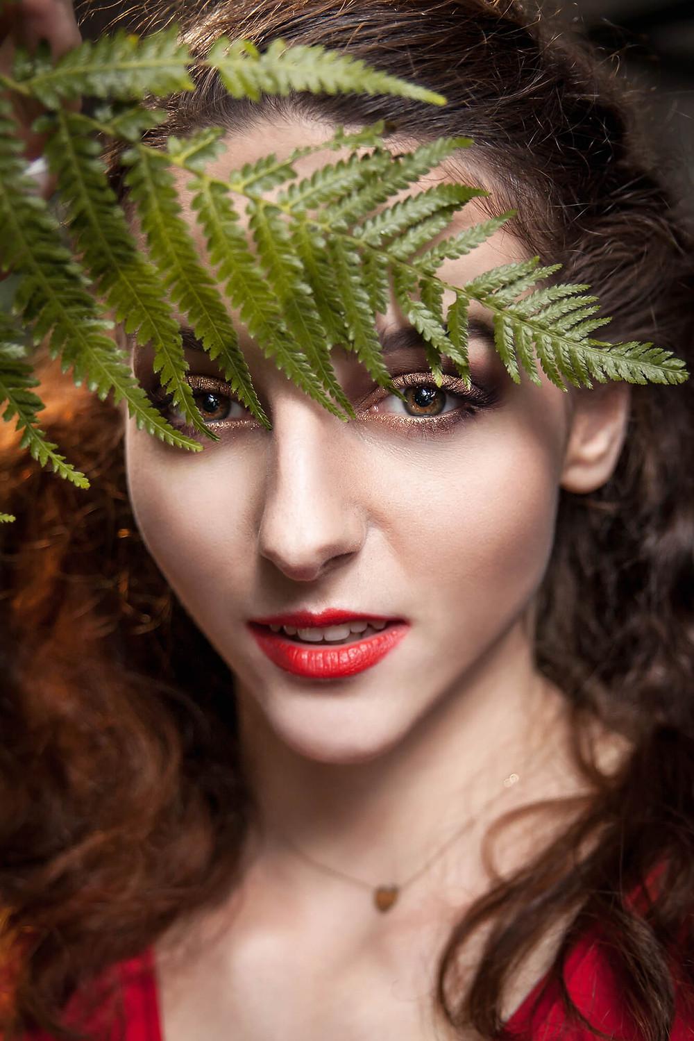 Zbliżenie na twarz modelki przesłoniętej liściem paproci