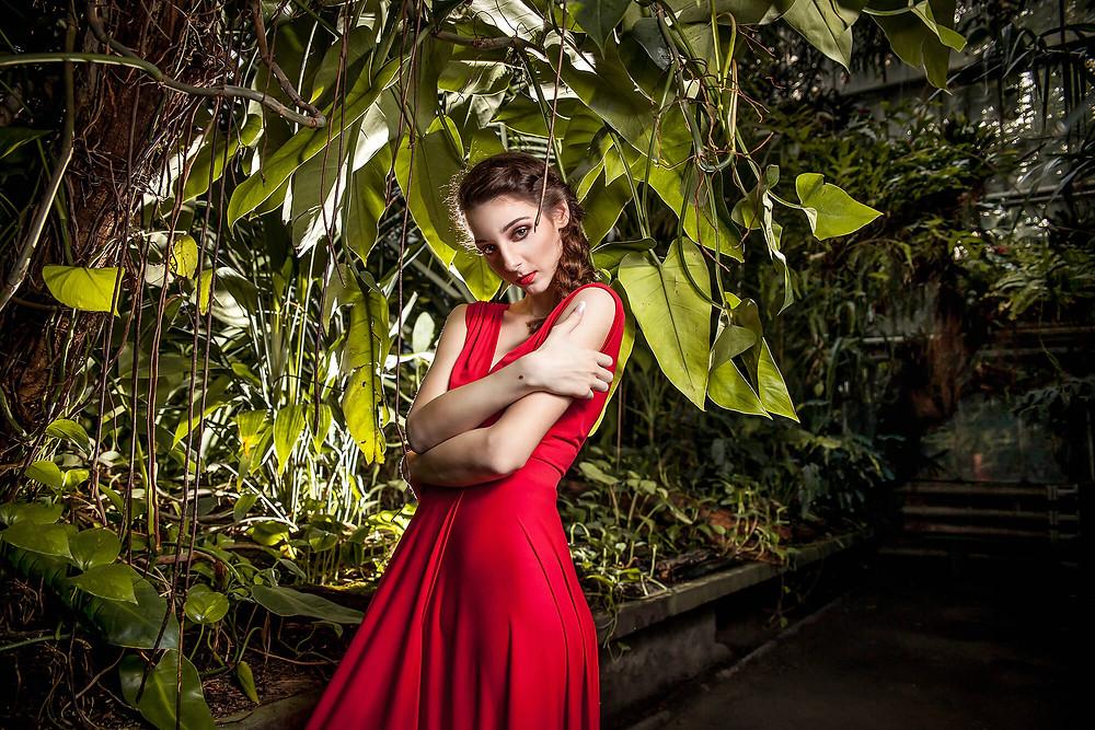 Modelka w czerwonej sukni pozuje wśród egzotycznych liści