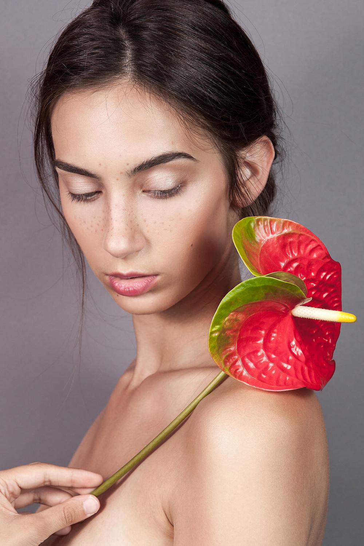 Piękne delikatne zdjęcie modelki trzymającej czerwony kwiat