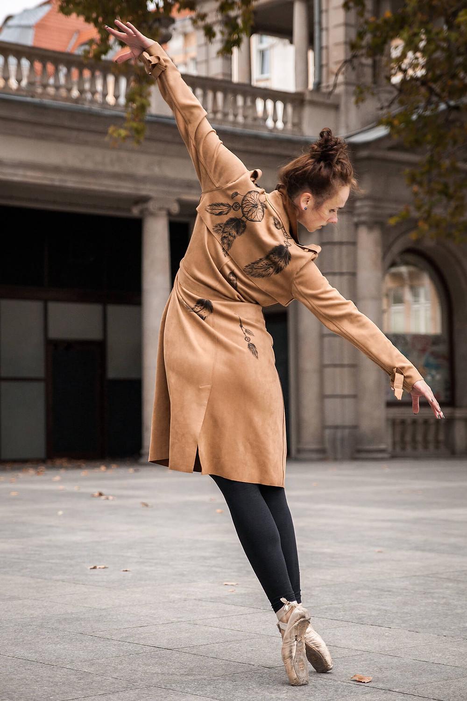 Baletowa poza off balance, tancerka w ręcznie malowanym płaszczu