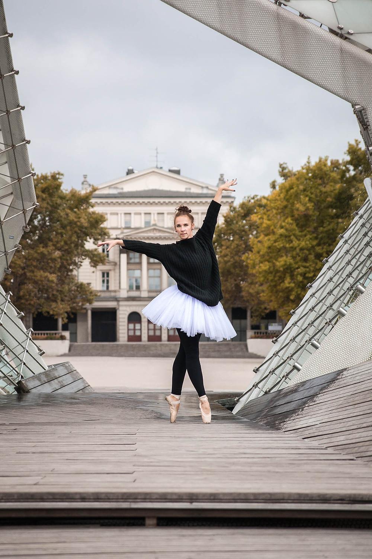 Tancerka w baletowej pozie stoi na tle Placu Wolności w Poznaniu