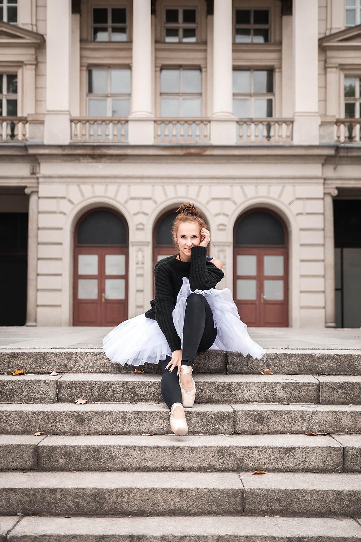 Uśmiechnięta baletnica siedzi na schodach przy Placu Wolności