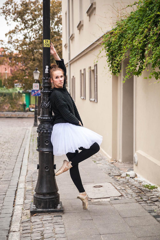 Tancerka w paczce i pointach opiera się o zabytkową latarnię