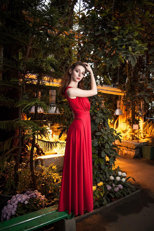 Modelka w czerwonej sukni na tle roślinności oświetlonej żółtym światłem