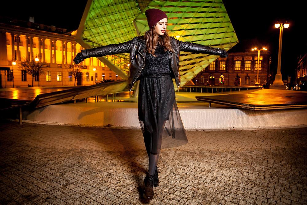 Nocna sesja zdjęciowa na Placu Wolności w Poznaniu, fontanna oświetlona na zielono, modelka pozuje z rozłożonymi rękami
