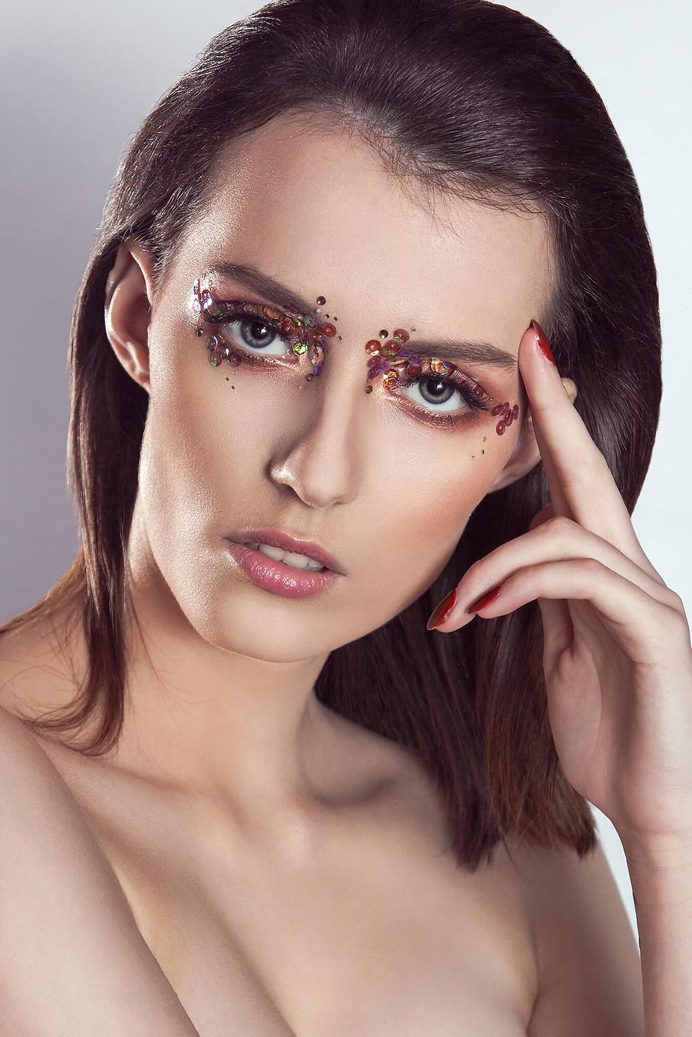 Piękna modelka z mocnymi oczami i delikatnymi ustami, złota sesja beauty
