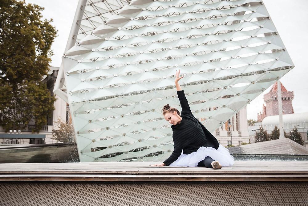 Tancerka w szpagacie na tle szklanej fasady