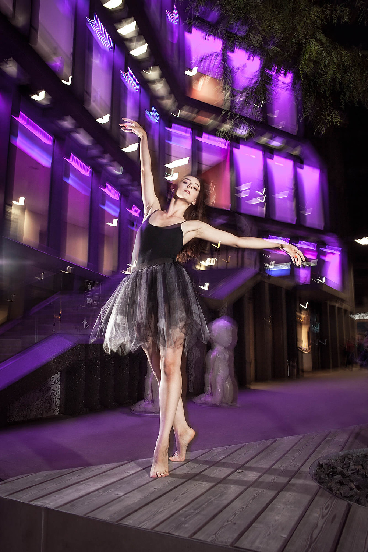 Taneczna poza, dynamiczne zdjęcie na tle oświetlonej architektury
