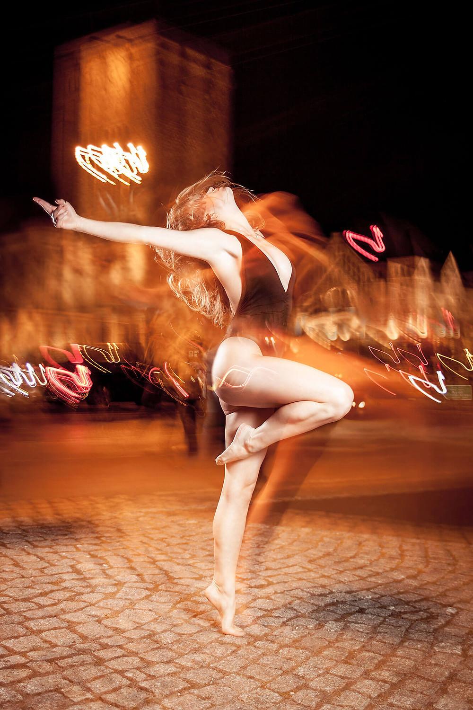 Tancerka wychyla się do tyłu stojąc na palcach jednej nogi, w tle rozmyte światła samochodów i ulicznych latarni