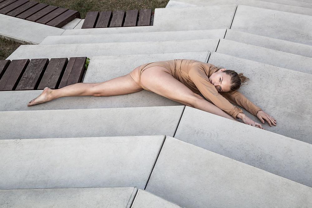 Tancerka leży w szlagacie na betonowych schodach