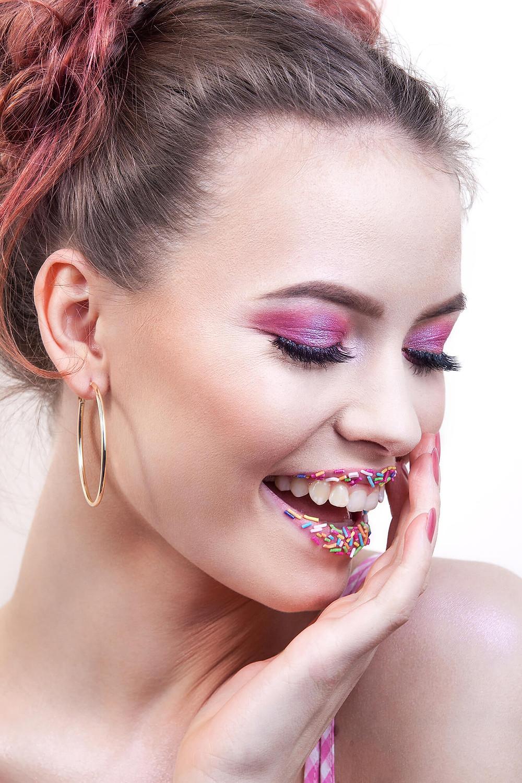 Roześmiana modelka z różowymi włosami i makijażem