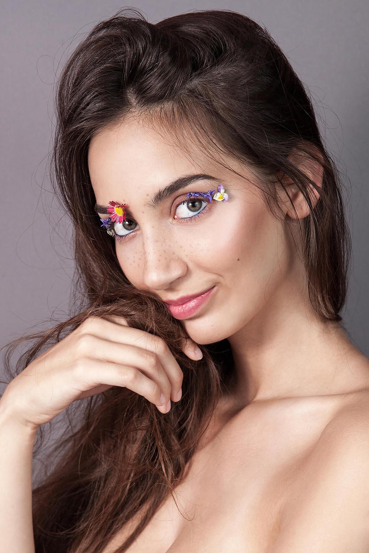 Uśmiechnięta, śliczna modelka z płatkami kwiatów na powiekach