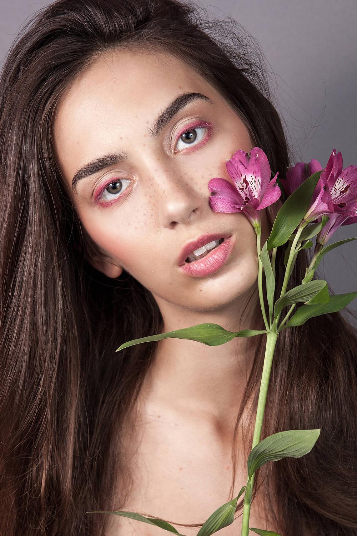 Wyraziste zdjęcie beauty z delikatnym makijażem i różowym kwiatem