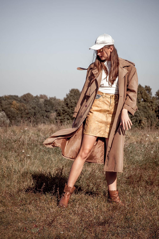 Modelka swobodnie pozuje przed obiektywem w długim, brązowym płaszczu
