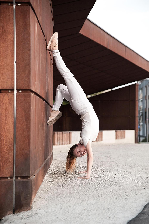 Tancerka contemporary stoi na rękach przy zardzewiałej, blaszanej ścianie