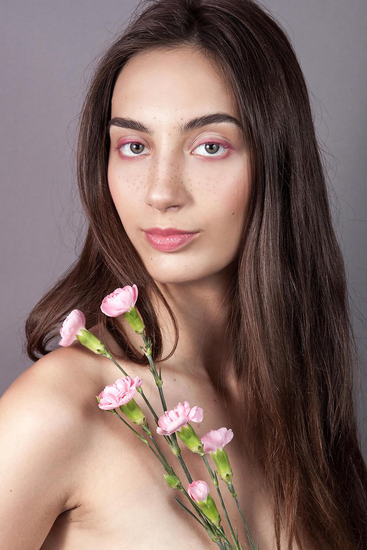 Sesja beauty z delikatnym, różowym makijażem i żywymi kwiatami