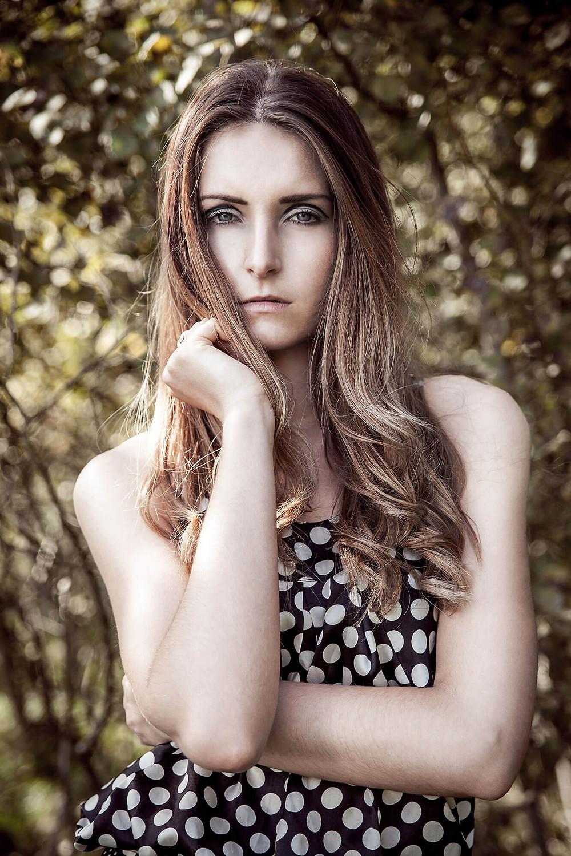 Portret pięknej modelki z rozwianymi, kręconymi włosami