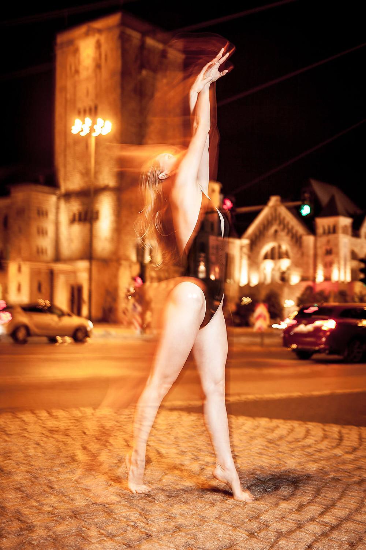 Tancerka stoi na palcach, ręce wyciągnięte do góry, w tle skrzyżowanie przed CK Zamek w Poznaniu