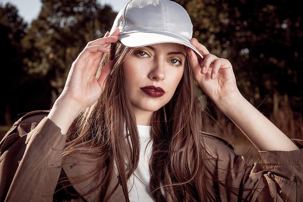 Modelka przytrzymuje czapkę z daszkiem i patrzy w obiektyw