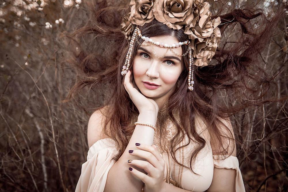 Dziewczyna w baśniowej stylizacji z włosami rozrzuconymi wokół głowy, aureola z włosów, korona z róż, baśniowa sesja zdjęciowa