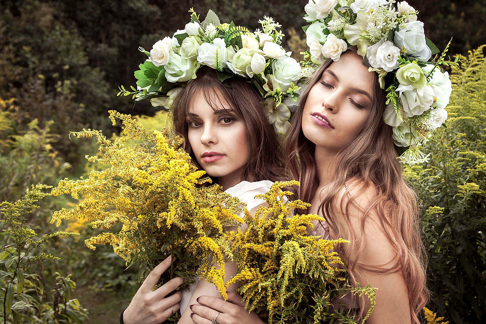 Portret wśród żółtych kwiatów z wiankami na głowie