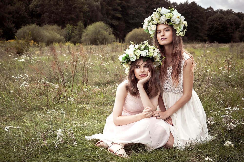 Piękne modelki w pastelowych sukienkach pozują na łące