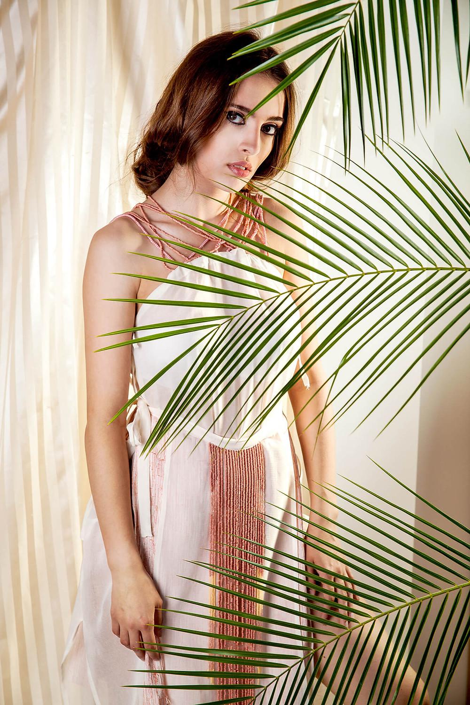 Modelka przesłonięta liśćmi palmy w sukience nawiązującej do starożytnego Egiptu
