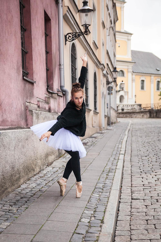 Tancerka w baletowej pozie stoi przy zabytkowych kamienicach