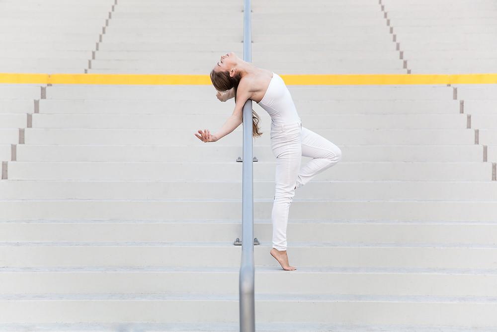 Tancerka na tle betonowych schodów wygina się do tyłu na poręczy