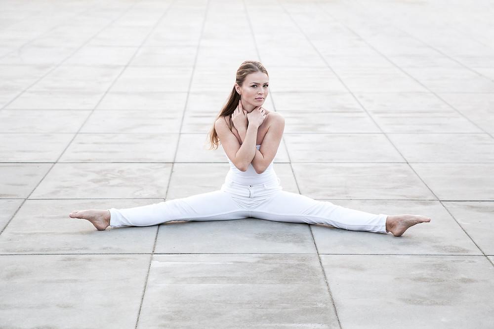 Tancerka w szpagacie na tle chodnikowych płytek