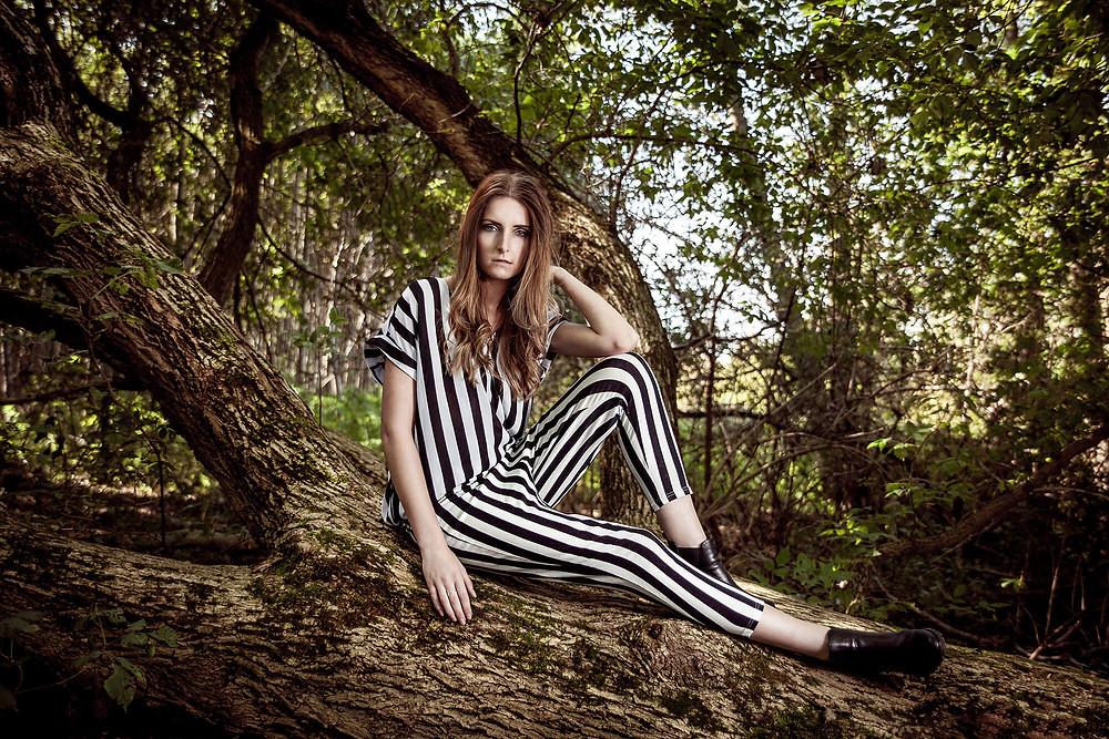 Modelka siedzi na powalonym drzewie i patrzy mocno w obiektyw