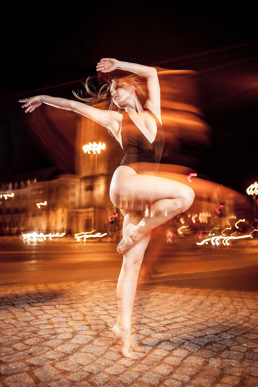 Taneczna sesja zdjęciowa, tancerka dynamicznie staje na palcach jednej nogi, w tle CK Zamek w Poznaniu, widoczne smugi spowodowane długim czasem naświetlania