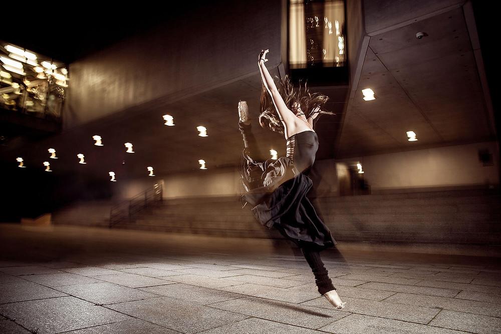 Tancerka ubrana na czarno skacze na tle współczesnej architektury