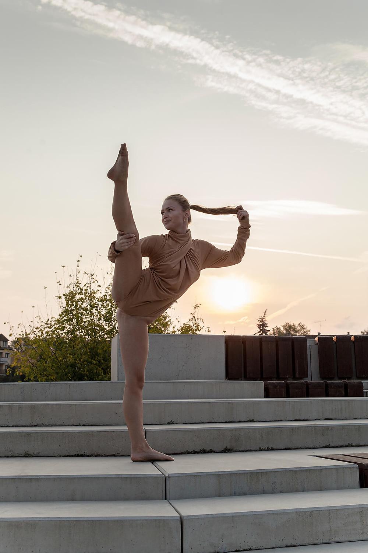 Tancerka unosi nogę do szpagatu, w tle wschodzące słońce