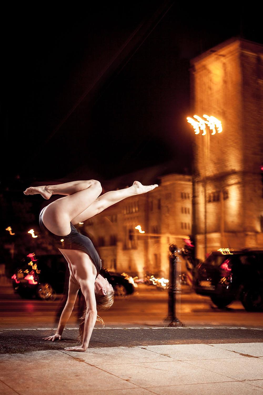 Tancerka contemporary, stanie na rękach z jedną nogą ugiętą, w tle ulica miasta nocą