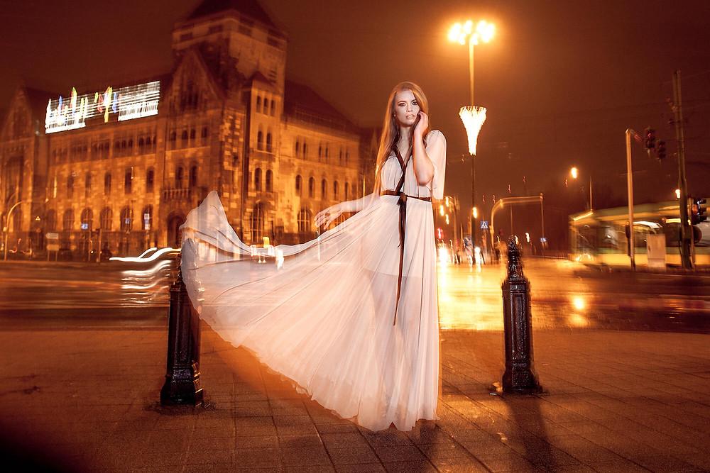 Modelka w zwiewnej sukni na tle nocnej, rozświetlonej ulicy
