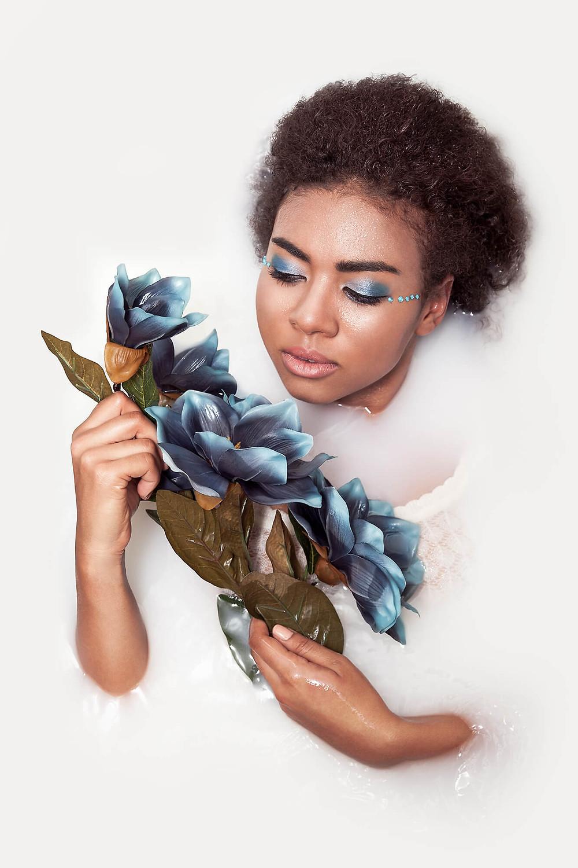 Ciemnoskóra modelka pozuje z niebieskim kwiatem w wannie mleka