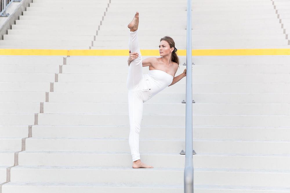 Tancerka unosi nogę do szpagatu i patrzy w dal na betonowych schodach