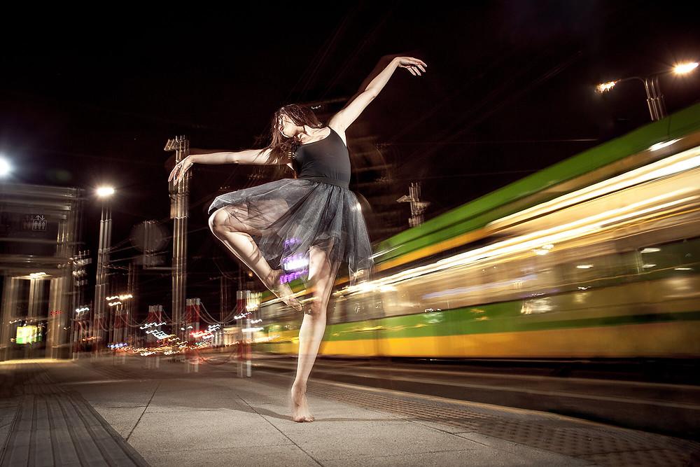 Sesja zdjęciowa tancerki z nogą na passe, w tle przejeżdżający szybko tramwaj