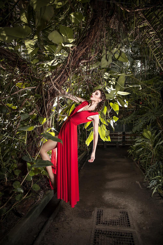 Edytorial fashion, modelka w długiej sukni zwisa z egzotycznego drzewa trzymając się gałęzi