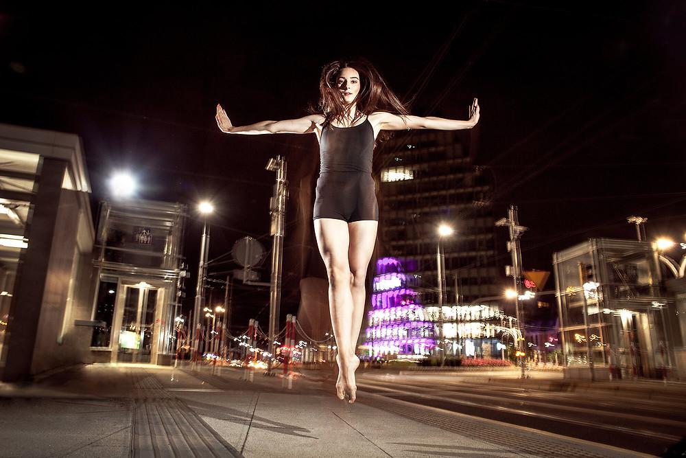 Symetryczny skok tancerki na tle oświetlonego nocą miasta