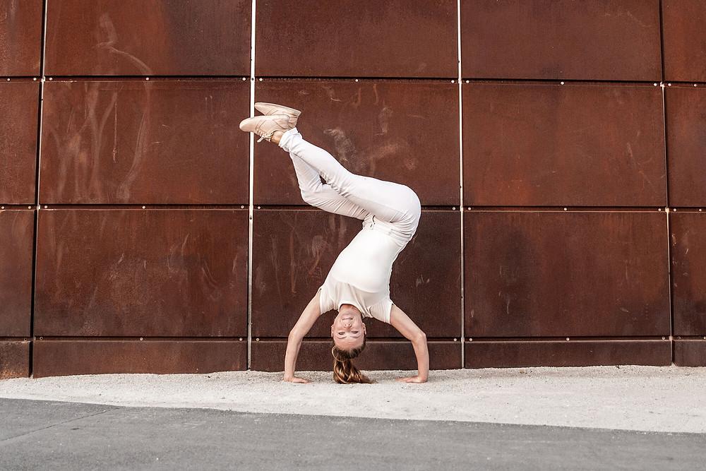 Tancerka stoi na rękach, w tle zardzewiałe blaszane płyty