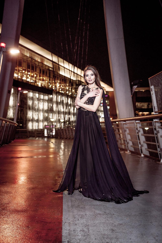 Dziewczyna w spektakularnej czarnej sukni pozuje na tle rozświetlonego budynku