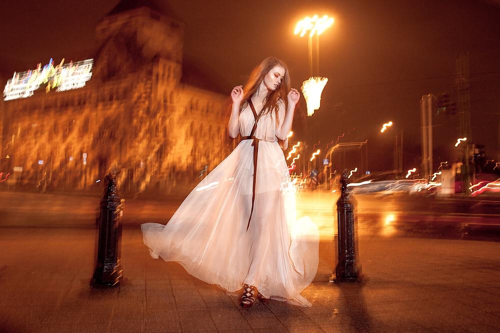 Długa, rozkloszowana suknia wieczorowa, sesja fashion w centrum miasta nocą