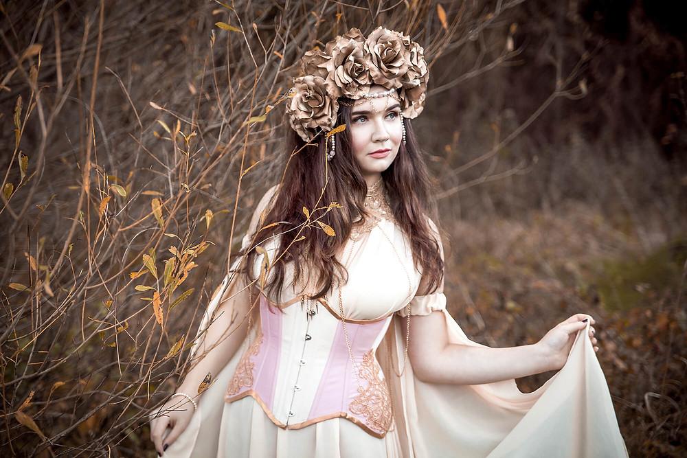 Baśniowa fotografia w Poznaniu, dziewczyna w beżowej sukni w blado różowym gorsecie ze złotymi różami na głowie