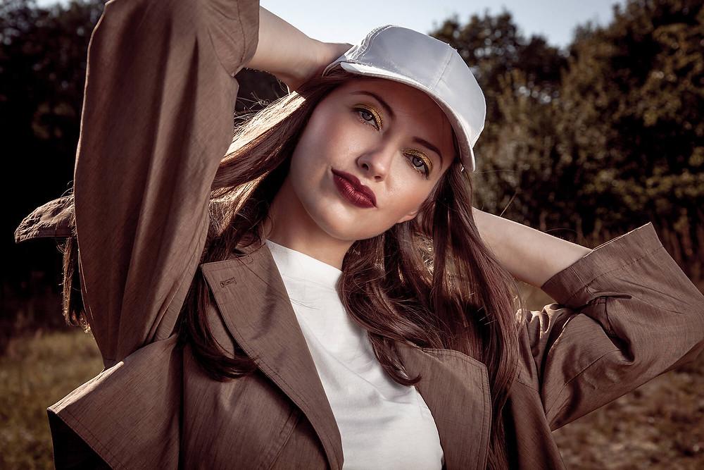 Pewna siebie modelka w czapce z daszkiem, modowa sesja zdjęciowa