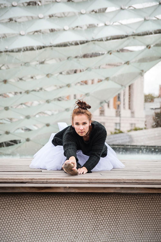 Baletnica w szpagacie patrzy w obiektyw, w tle szklana ściana fontanny