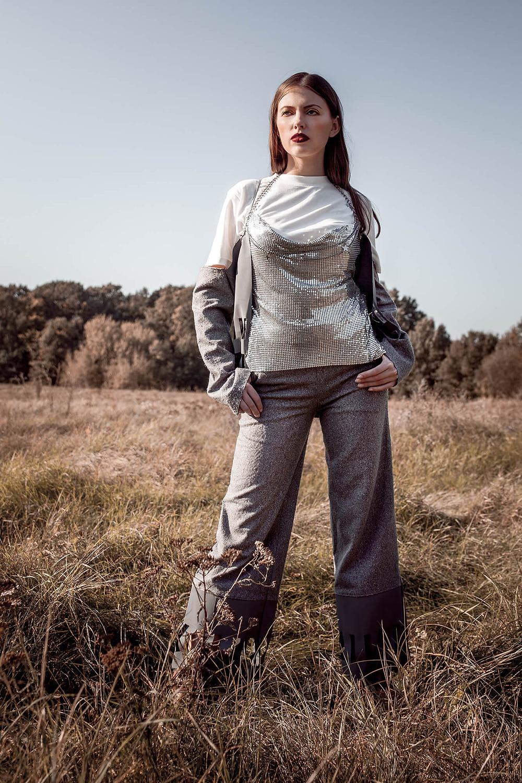 Pewna siebie modelka stoi na łące w lśniącej, srebrnej stylizacji