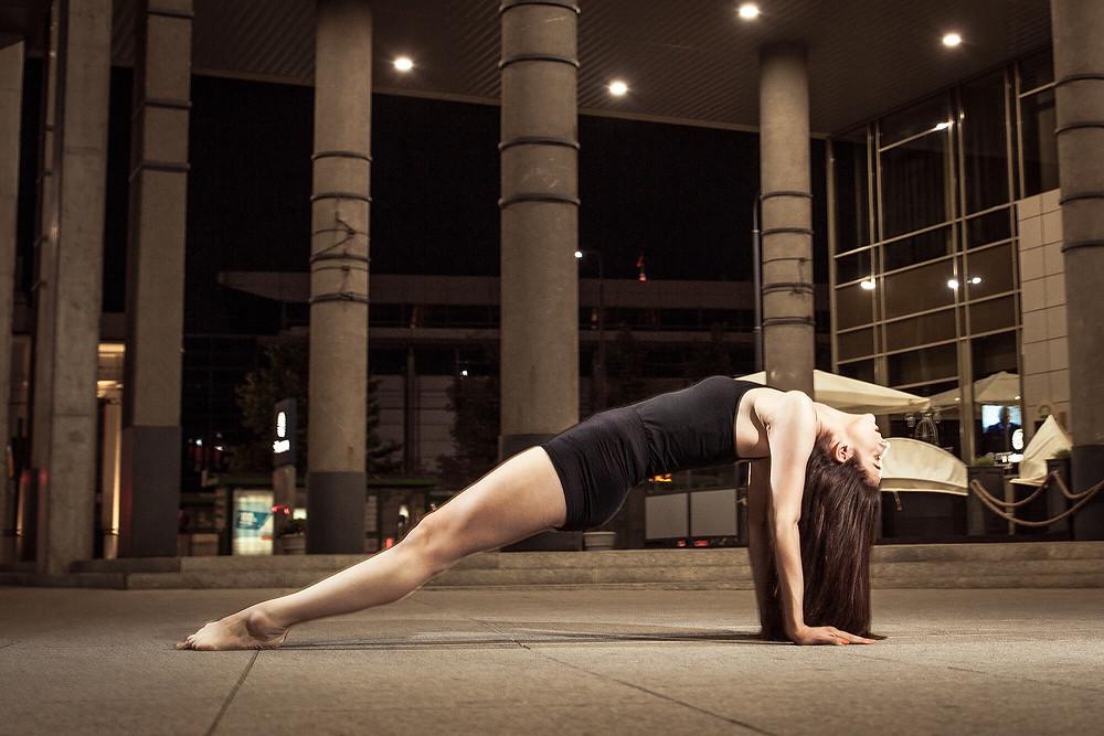 Tancerka w planku tyłem na tle betonowych kolumn